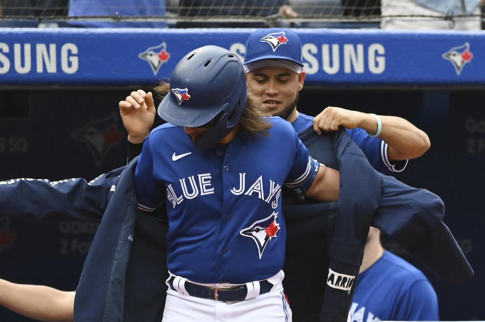 Toronto Blue Jays' Breyvic Valera, right, puts The Blue Jacket on Bo Bichette after Bichette hit a three-run home run in the first inning of a baseball game against the Tampa Bay Rays in Toronto on Wednesday, Sept. 15, 2021. (Jon Blacker/The Canadian Press via AP)