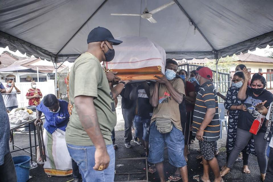 Pallbearers carry a coffin containing the remains of Sivabalan Subramaniam.