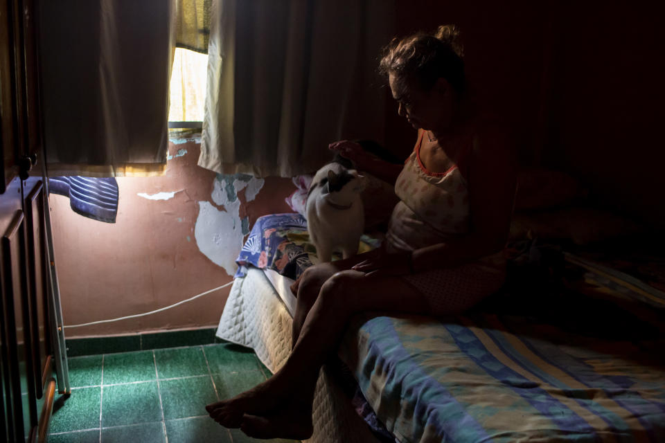 Diana dos Santos, 71, sits with her cat Pepinha in her home where she lives in social isolation, in the Mare neighborhood of Rio de Janeiro, Brazil, Saturday, Aug. 28, 2021, amid the new coronavirus pandemic. She refuses to leave her home until she gets a booster of the COVID-19 vaccine. (AP Photo/Bruna Prado)