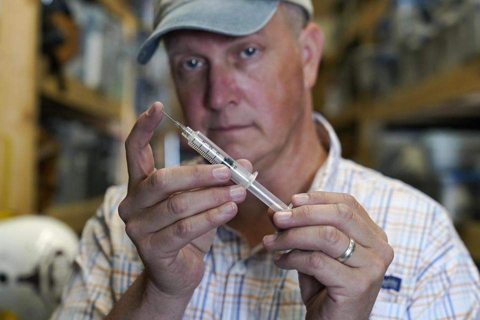 Movie prop master Scott Reeder displays a retractable stunt syringe and needle at his shop in Austin, Texas, on April 26, 2021. Reeder's TikTok video about prop retractable needles was used without his permission to spread false claims about politicians getting fake vaccinations. Individuals across the country, like Reeder, have found themselves swept into the misinformation maelstrom, their online posts or their very identities hijacked by anti-vaccine activists and others peddling lies about the COVID-19 outbreak. (AP Photo/Eric Gay)