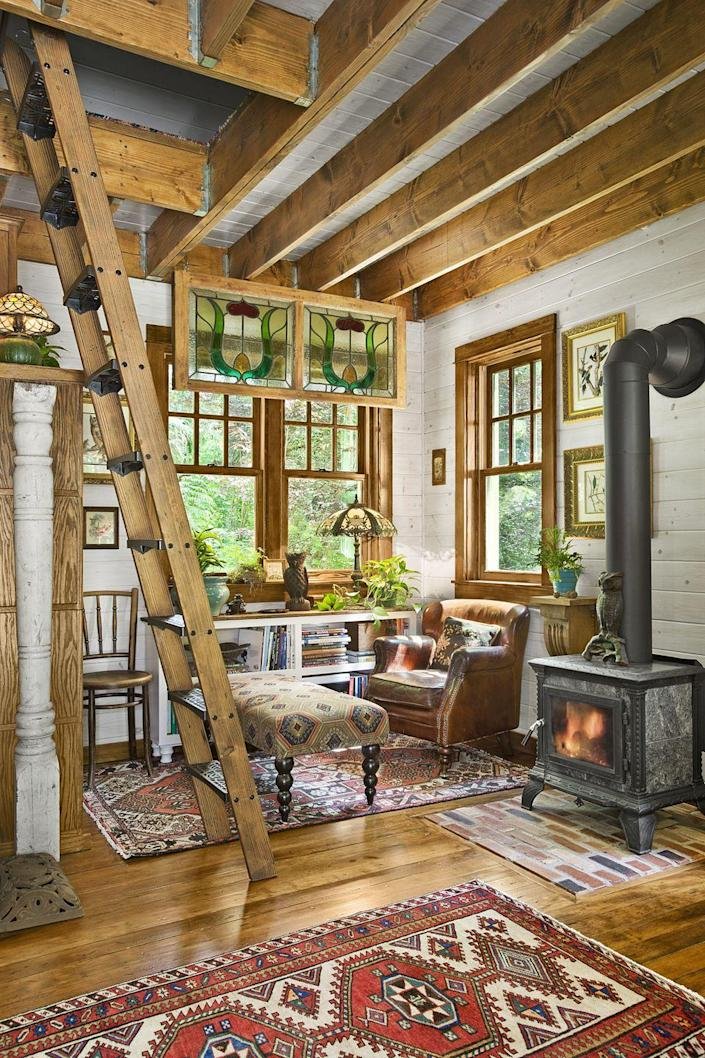 """<p>When square footage is tight, it helps if statement pieces are both charming and useful. An old wood-burning stove brings a vintage vibe to new construction and also heats the entire place.</p><p><a class=""""link rapid-noclick-resp"""" href=""""https://www.amazon.com/Tiny-House-Living-Building-Square/dp/1440333165/?tag=syn-yahoo-20&ascsubtag=%5Bartid%7C10072.g.35047961%5Bsrc%7Cyahoo-us"""" rel=""""nofollow noopener"""" target=""""_blank"""" data-ylk=""""slk:SHOP TINY HOUSE BOOKS"""">SHOP TINY HOUSE BOOKS</a></p>"""