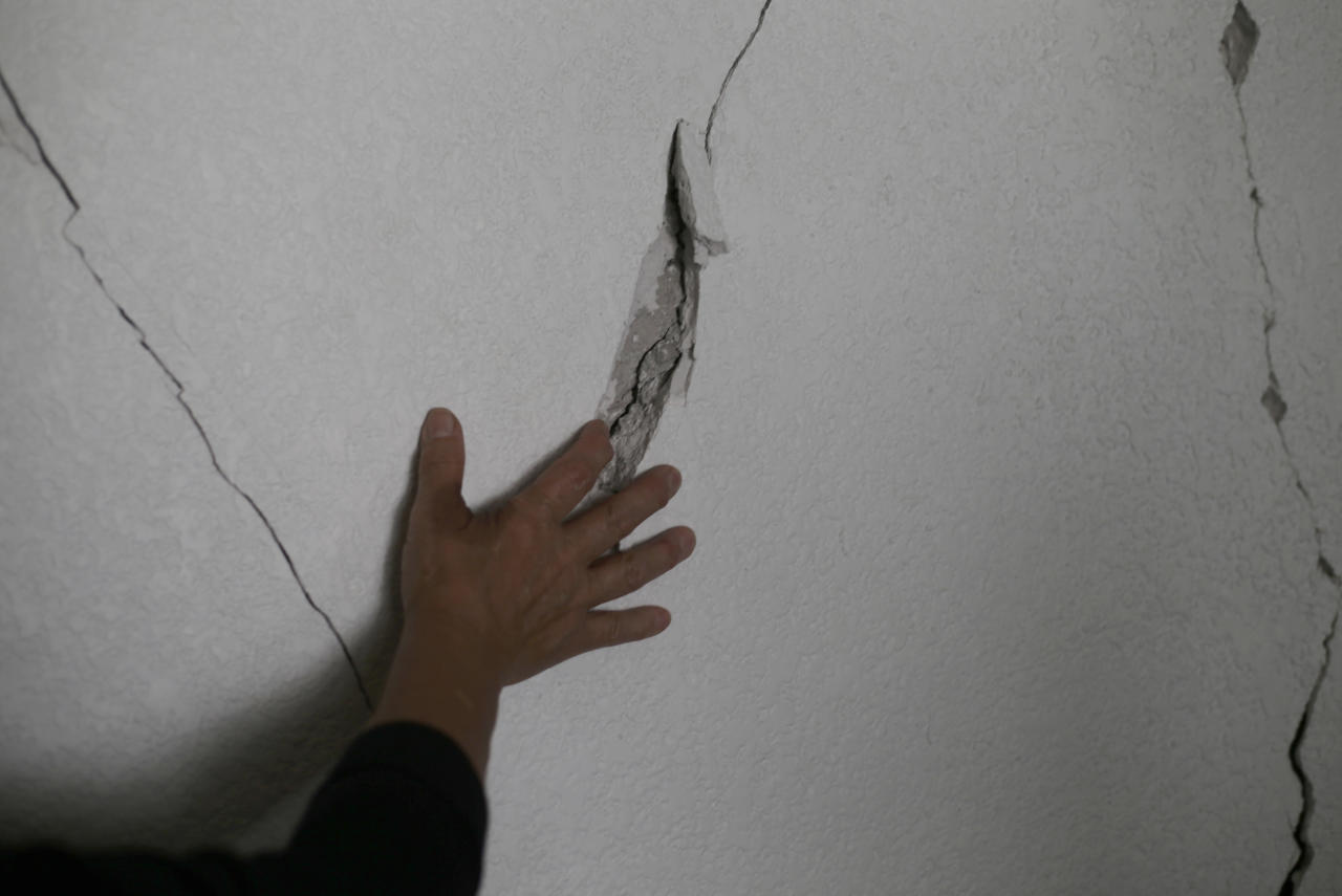 In this Oct. 17 photo, Maria Luisa Campuzano Fernandez runs her hand over cracks in her apartment wall at 275 Monterrey street in the Roma neighborhood of Mexico City. Campuzano has been staying in a hotel since the Sept. 19 earthquake damaged the apartment building where she had lived for 15 years. (AP Photo/Marco Ugarte)