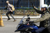 Brazil's President Jair Bolsonaro, waves as he leads a caravan of motorcycle enthusiasts following him through the streets of the city, in a show of support for Bolsonaro, in Sao Paulo, Brazil, Saturday, June 12, 2021. (AP Photo/Marcelo Chello)