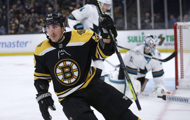 Boston Bruins left wing Brad Marchand, left, raises his stick after a goal against San Jose Sharks goaltender Martin Jones, right, during the second period of an NHL hockey game in Boston, Tuesday, Feb. 26, 2019. (AP Photo/Charles Krupa)
