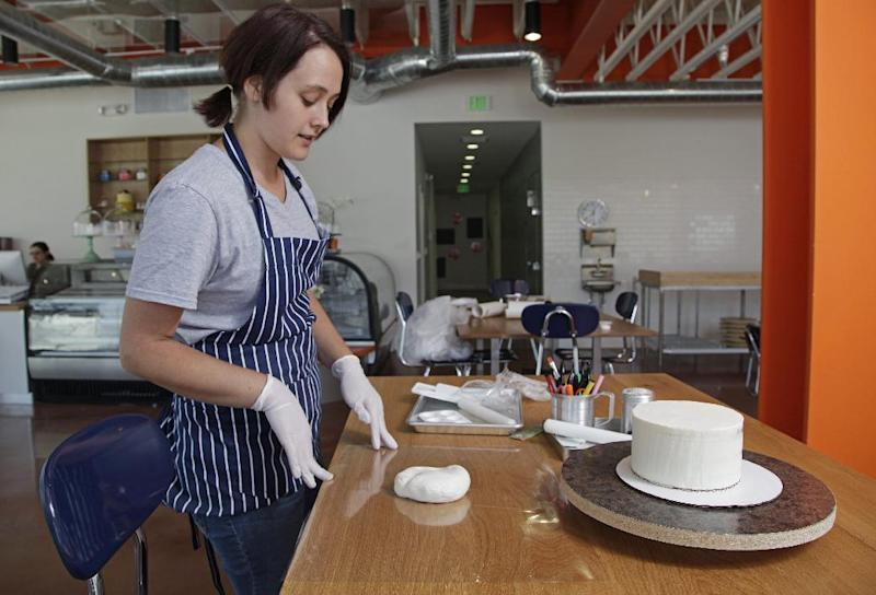 This image taken on Wednesday, June 20, 2012, shows Duff team member, Katlyn Beggs, preparing a make-your-own cake at chef and owner, Duff Goldman's new venture, Duff's Cakemix, in Los Angeles. (AP Photo/Damian Dovarganes)