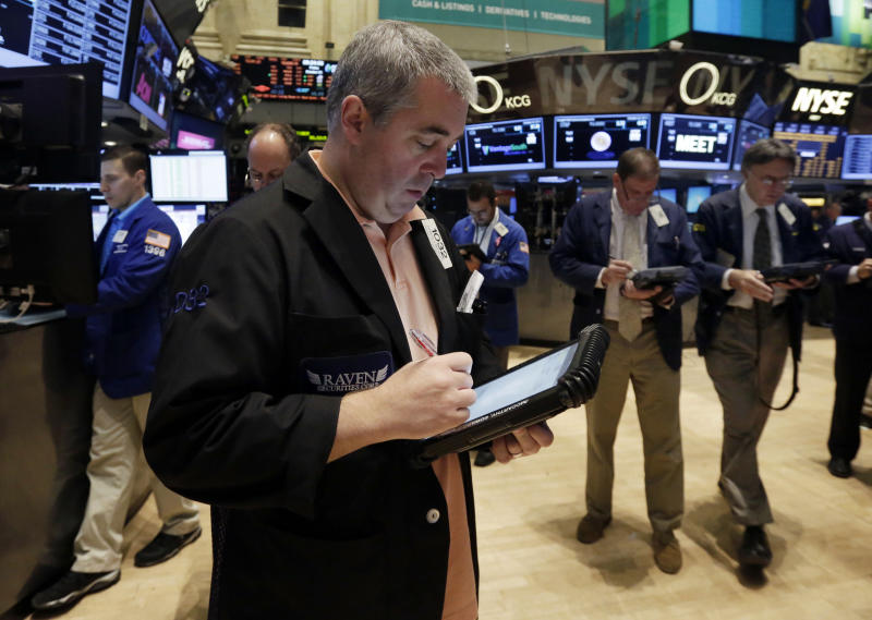 Trader Edward McCarthy, forground, works on the floor of the New York Stock Exchange, Friday, Oct. 25, 2013. Earnings gains from Microsoft and other big U.S. companies are pushing the stock market higher in early trading. (AP Photo/Richard Drew)
