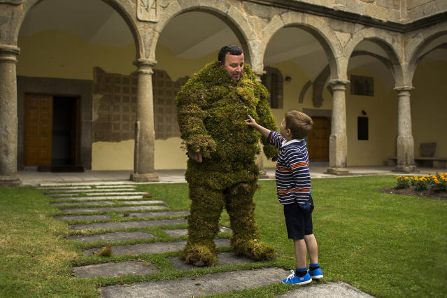 <p>A moss man plays with his son before taking part in the Corpus Christi procession in the village of Bejar, Spain, June 7, 2015. (AP Photo/Andres Kudacki) </p>