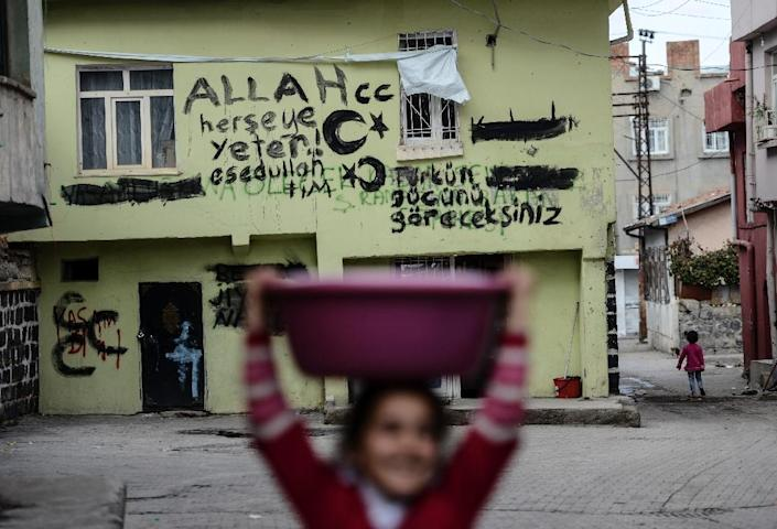 """A building covered in slogans said to be written by Turkish special forces reading on the right, """"You will see the power of Turks"""" and on the left ''God enough for everything'' in Diyarbakir, southeastern Turkey, on October 31, 2015 (AFP Photo/Bulent Kilic)"""