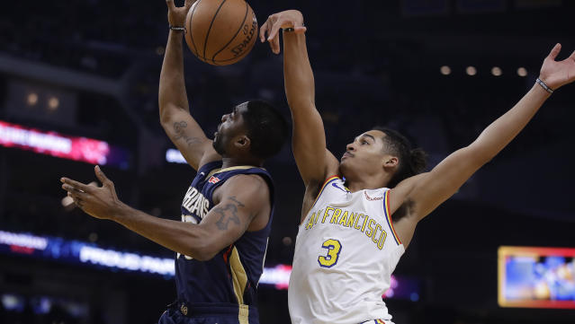New Orleans Pelicans' E'Twaun Moore, left, lays up a shot past Golden State Warriors' Jordan Poole (3) during the first half of an NBA basketball game Friday, Dec. 20, 2019, in San Francisco. (AP Photo/Ben Margot)