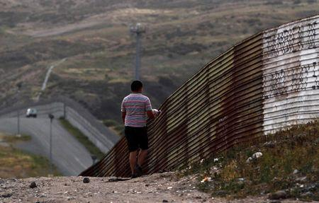 A resident walks by a section of the border fence between Mexico and the United States on the outskirts of Tijuana, Mexico April 5, 2016. REUTERS/Jorge Duenes