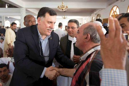Unity government head Fayez Seraj (L) shakes hands with a man inside a mosque after Friday prayers, during a tour in Tripoli city, Libya, April 1, 2016, in this handout photo provided by the Office of Information. REUTERS/Office of Information/Handout via Reuters