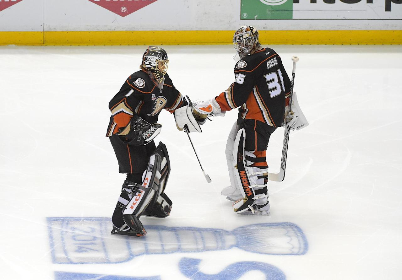 Anaheim Ducks goalie John Gibson, right, leaves the ice as goalie Jonas Hiller, of Switzerland, skates on as the Ducks change goalies during the second period in Game 7 of an NHL hockey second-round Stanley Cup playoff series against the Los Angeles Kings, Friday, May 16, 2014, in Anaheim, Calif. (AP Photo/Mark J. Terrill)
