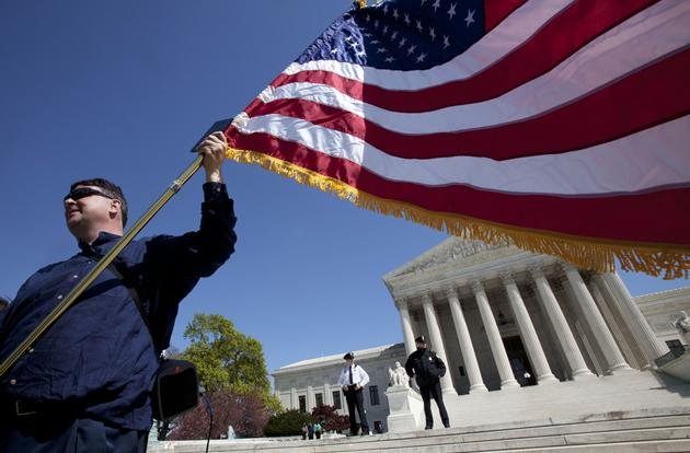 Holding an American flag and a copy of the Constitution, Dan, who asked not to use his last name, of Virginia, protests against the health care law.