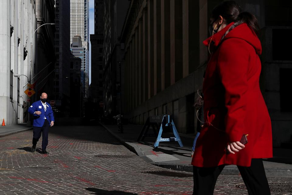 A trader wearing a protective face mask walks, as the global outbreak of the coronavirus disease (COVID-19) continues, outside the New York Stock Exchange (NYSE)  in the financial district of New York, U.S., November 19, 2020. REUTERS/Shannon Stapleton