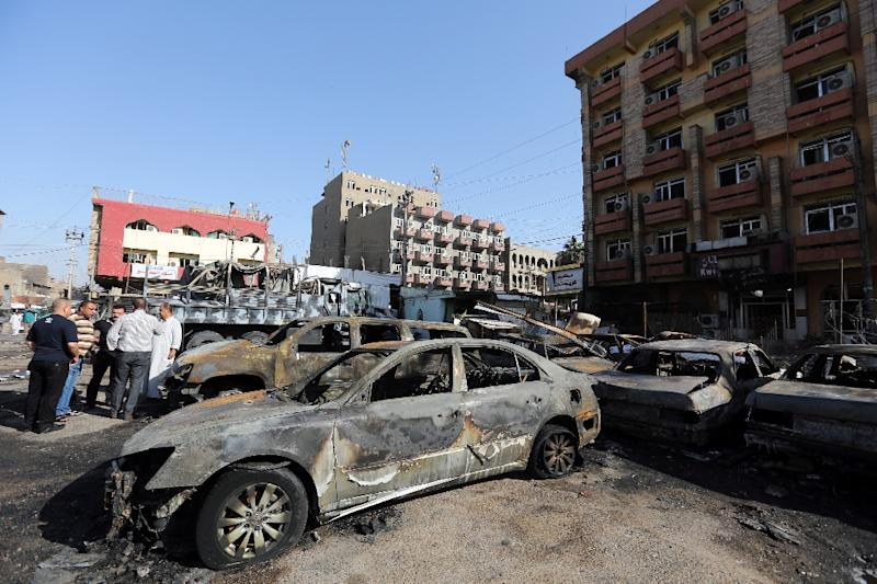 Burnt cars are seen at the site of a car bomb explosion near a liquor store in central Baghdad's Battaween area early on September 29, 2015, which killed at least two people
