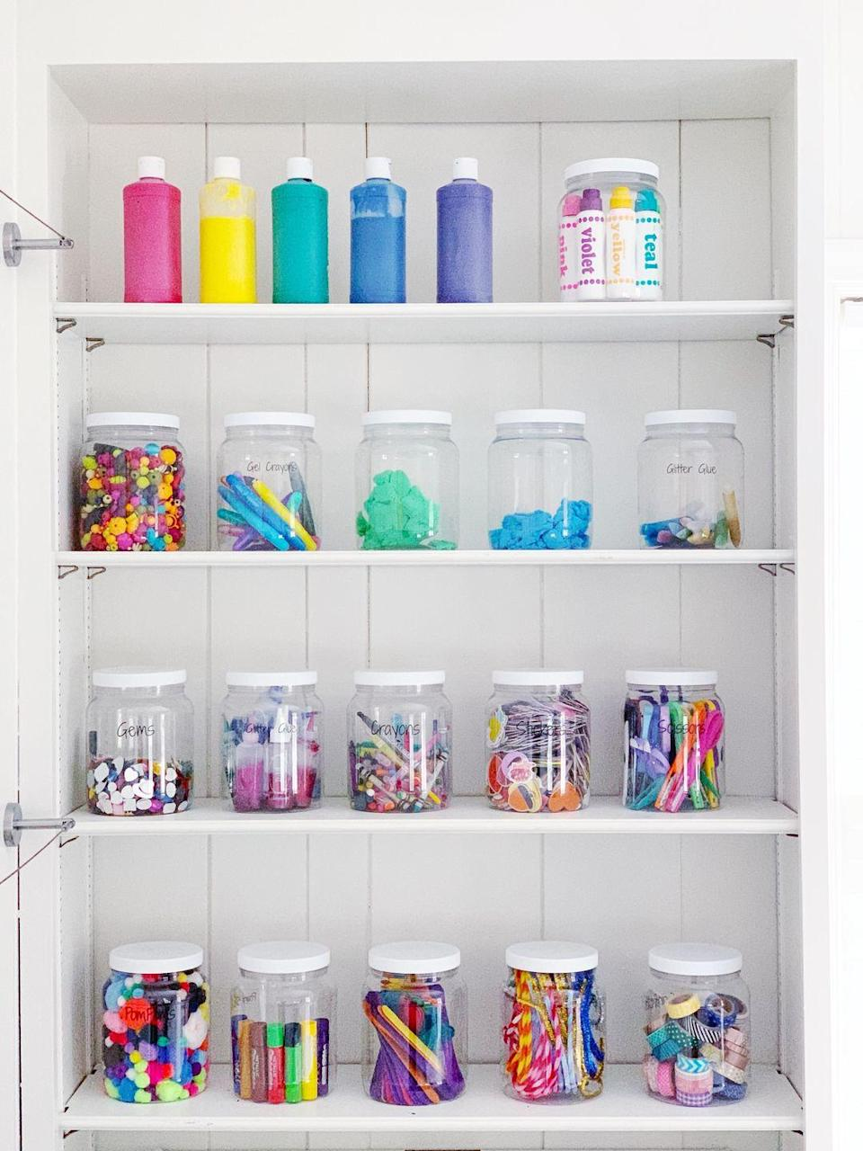 """<p>By storing kids' art supplies in clear jars, you'll always know exactly how many pom-poms, pipe cleaners, and Popsicle sticks you have in stock.</p><p><strong>See more at <a href=""""https://www.styleanddwell.com/craft-room-organization/"""" rel=""""nofollow noopener"""" target=""""_blank"""" data-ylk=""""slk:Style + Dwell"""" class=""""link rapid-noclick-resp"""">Style + Dwell</a>.</strong></p><p><strong><a class=""""link rapid-noclick-resp"""" href=""""https://www.amazon.com/1790-Half-Gallon-Glass-2-Pack/dp/B07NQR7L71?tag=syn-yahoo-20&ascsubtag=%5Bartid%7C10063.g.36014277%5Bsrc%7Cyahoo-us"""" rel=""""nofollow noopener"""" target=""""_blank"""" data-ylk=""""slk:SHOP HALF-GALLON JARS"""">SHOP HALF-GALLON JARS</a><br></strong></p>"""