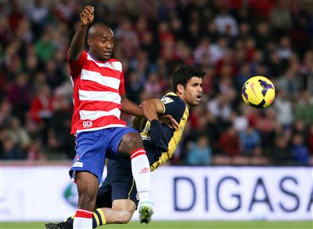 Atletico Madrid's Diego Costa (R) is challenged by Granada's Dimitri Foulquier during their Spanish First Division soccer match at Nuevo Los Carmenes stadium in Granada October 31, 2013. REUTERS/Pepe Marin