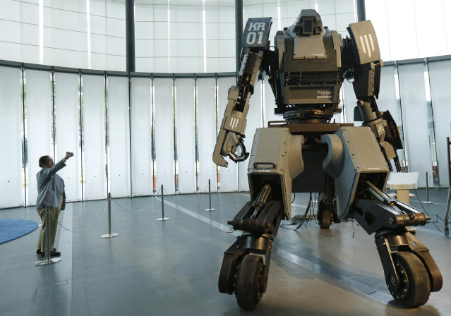 "A man takes a picture of a giant ""Kuratas"" robot at an exhibition in Tokyo November 28, 2012. The four-meter-high, limited edition, made-to-order robot is controlled through a pilot in its cockpit, or via a smartphone. The four-tonne (4,000 kg) ""Kuratas"" can be customised in 16 different colours, and is armed with a futuristic weapons system, including a multi-rocket launcher that fires plastic rockets filled with compressed water. REUTERS/Kim Kyung-Hoon (JAPAN - Tags: SOCIETY SCIENCE TECHNOLOGY TPX IMAGES OF THE DAY)"