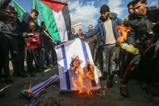 Palestinians angry at controversial peace proposals unveiled by US President Donald Trump burn an Israeli flag during a protest in the Gaza Strip city of Khan Yunis