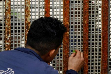 FILE PHOTO: A man who was deported from the U.S. seven months ago, receives candy from his nephew across a fence separating Mexico and the U.S, in Tijuana