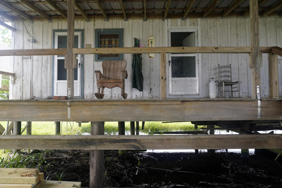 A rocking chair sits on the porch of an old trapper's camp that has been restored and repurposed by the McIlhenny Company, on Avery Island, La., where Tabasco brand pepper sauce is made, Tuesday, April 27, 2021. As storms grow more violent and Louisiana loses more of its coast, the family that makes Tabasco Sauce is fighting erosion in the marshland that buffers its factory from hurricanes and floods. (AP Photo/Gerald Herbert)