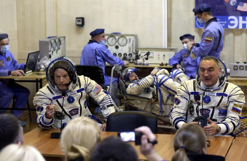 Members of the International Space Station (ISS) crew, U.S. astronaut Steven Swanson (L) and Russian cosmonaut Alexander Skvortsov (R) speak with relatives as Russian cosmonaut Oleg Artemyev (C) tests a space suit during pre-launch preparations at the Baikonur cosmodrome March 25, 2014. REUTERS/Maxim Shipenkov/Pool (KAZAKHSTAN - Tags: SCIENCE TECHNOLOGY TRANSPORT)