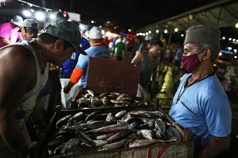 Vendors and customers trade fishes at Panair Municipal Market in Manaus, Amazonas state, Brazil, on June 17, 2020, amid the new coronavirus (COVID-19) pandemic. (Photo by MICHAEL DANTAS / AFP) (Photo by MICHAEL DANTAS/AFP via Getty Images)