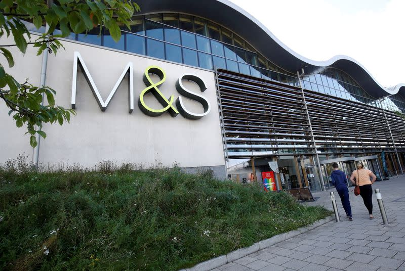FILE PHOTO: People walk outside a Marks and Spencer (M&S) store in Cheshire
