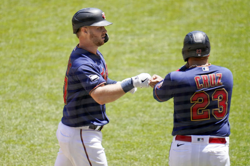 Minnesota Twins' Ryan Jeffers, left, and Nelson Cruz fist bump after Jeffers' two-run home run off Cincinnati Reds' pitcher Wade Miley in the fourth inning of a baseball game, Tuesday, June 22, 2021, in Minneapolis. (AP Photo/Jim Mone)