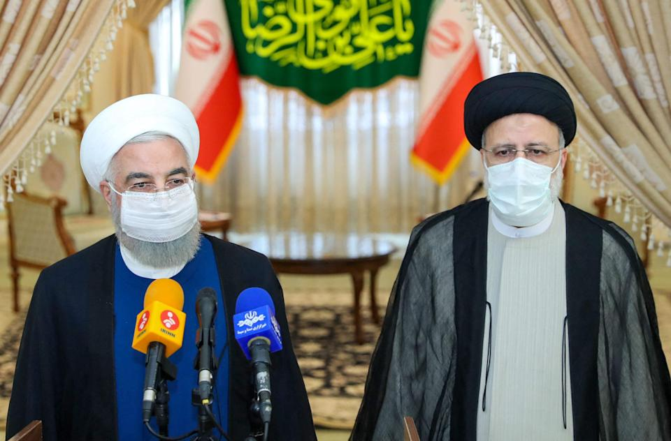Outgoing president Hassan Rouhani (L) takes part in a press conference with president-elect Ebrahim Raisi  (Iranian Presidency/AFP/Getty)
