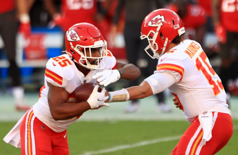 Patrick Mahomes #15 of the Kansas City Chiefs hands the ball to teammate Clyde Edwards-Helaire #25