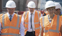 Britain's Prime Minister Boris Johnson, centre, during a visit to a construction site, in Hereford, England, Tuesday, Aug. 11, 2020. Hereford County Hospital is expanding with a three storey modular building providing 72 new beds over three wards under construction. The new facility will open early 2021. (Matthew Horwood/Pool Photo via AP)