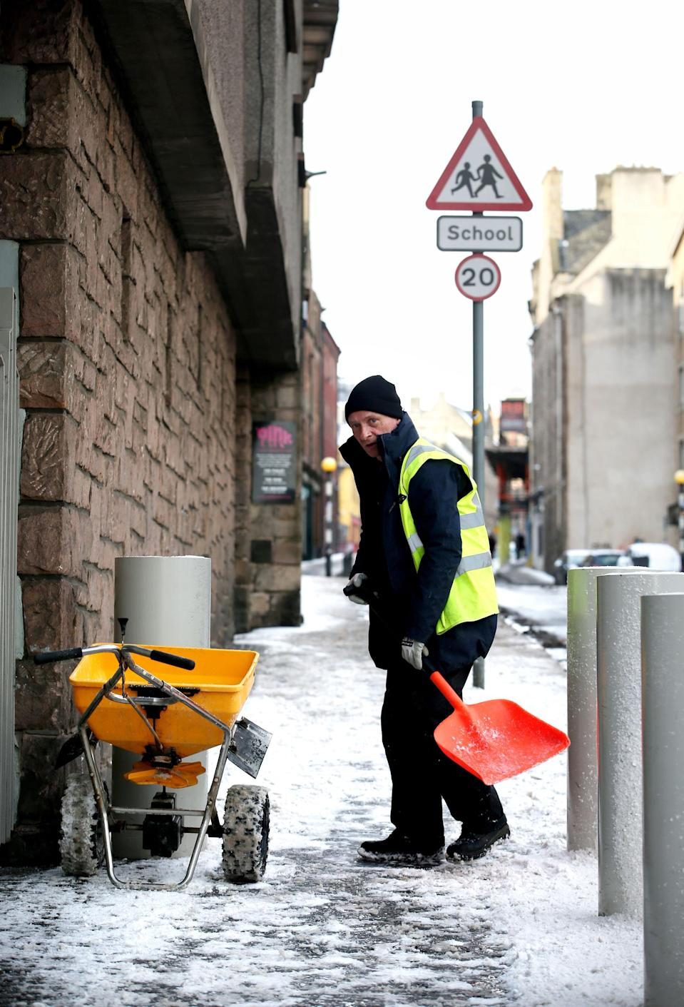 <p>A man clears snow from pavements along Edinburgh's Royal Mile. Weather warnings for snow are still in place with northern England and Scotland set to be hit the hardest. (PA) </p>