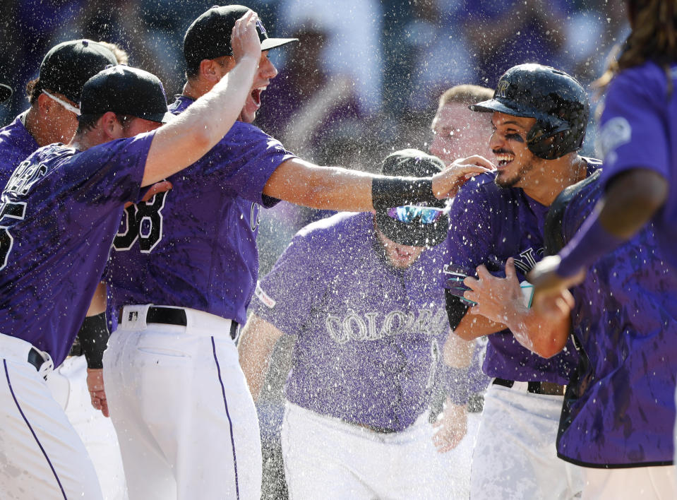 Colorado Rockies' Nolan Arenado, right, is congratulated by teammates after his game-ending two-run home run off Arizona Diamondbacks relief pitcher Archie Bradley during the ninth inning of a baseball game Wednesday, Aug. 14, 2019, in Denver. The Rockies won 7-6. (AP Photo/David Zalubowski)