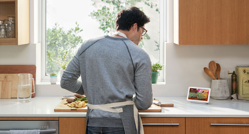 man cooking in kitchen wearing apron looking at google nest device