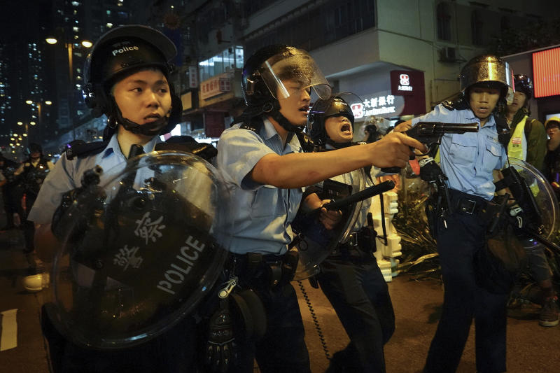 Policemen pull out their guns after a confrontation with demonstrators during a protest in Hong Kong, Sunday, Aug. 25, 2019. Hong Kong police have rolled out water cannon trucks for the first time in this summer's pro-democracy protests. The two trucks moved forward with riot officers Sunday evening as they pushed protesters back along a street in the outlying Tsuen Wan district. (AP Photo/Vincent Yu)