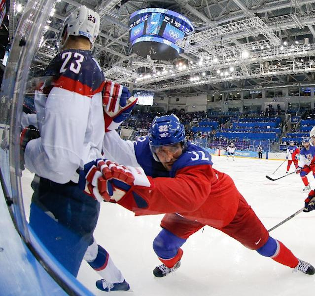 Czech Republic defenseman Michal Rozsival pins USA forward Dustin Brown agains the glass during the second period of men's quarterfinal hockey game in Shayba Arena at the 2014 Winter Olympics, Wednesday, Feb. 19, 2014, in Sochi, Russia. (AP Photo/Petr David Josek)