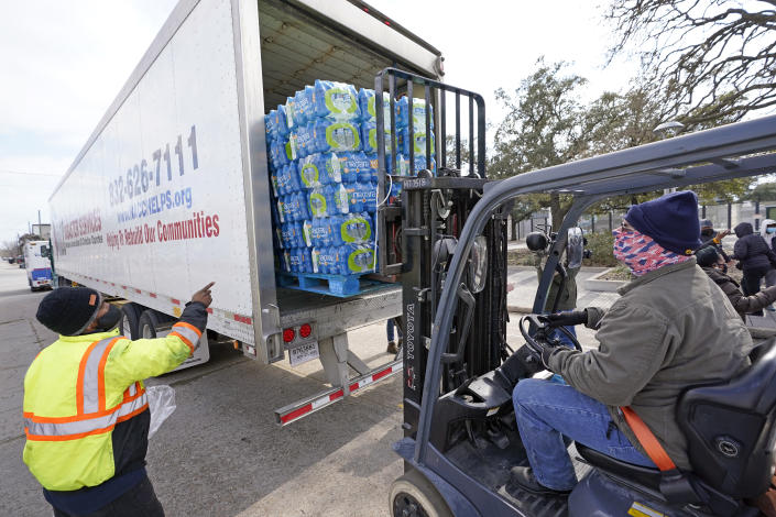 Donated water is unloaded at a distribution site, Thursday, Feb. 18, 2021, in Houston. Houston and several surrounding cities are under a boil water notice as many residents are still without running water in their homes. (AP Photo/David J. Phillip)
