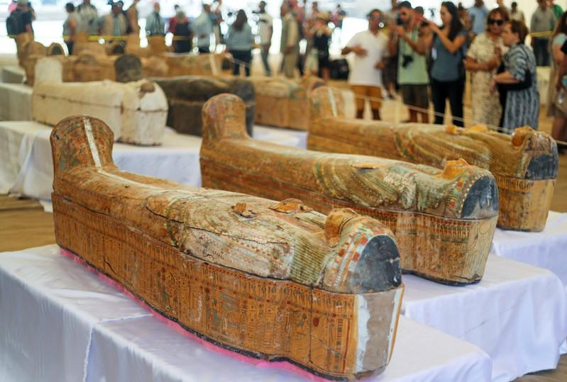Tourists look at painted ancient coffins at Al-Asasif necropolis, unveiled by Egyptian antiquities officials in the Valley of the Kings in Luxor