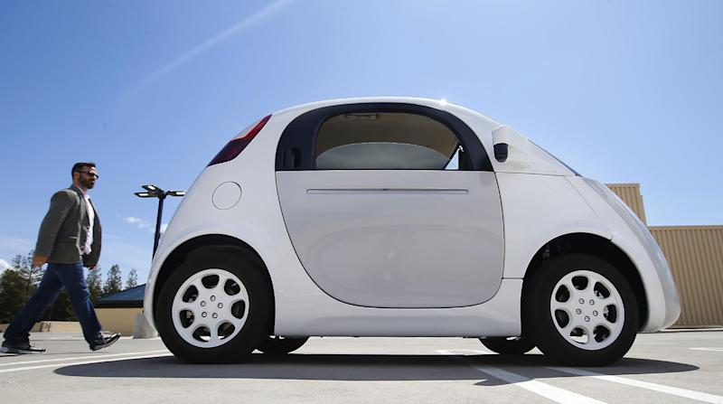 In this May 13, 2015 photo, a reporter walks toward Google's new self-driving prototype car during a demonstration at the Google campus in Mountain View, Calif. The car, which needs no gas pedal or steering wheel, will make its debut on public roads this summer. (AP Photo/Tony Avelar)