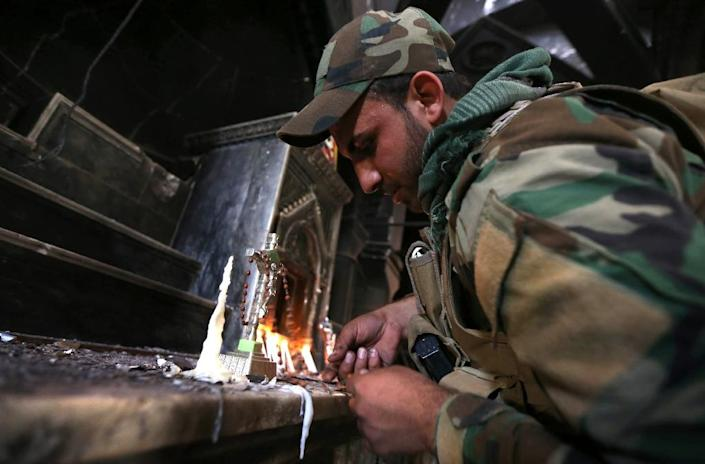 An Iraqi Christian forces member lights a candle at the Church of the Immaculate Conception on October 30, 2016 in the town of Qaraqosh, 30 kms east of Mosul, after Iraqi forces recaptured it from the Islamic State (AFP Photo/Safin Hamed)