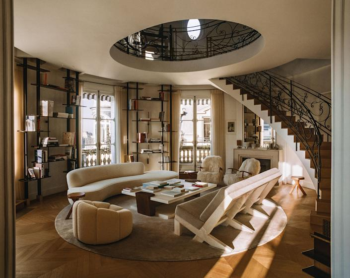 Designer Isabelle Stanislas opened the living-room ceiling to the dome above and connected them with a dramatic curving staircase. Vladimir Kagan sofa; Christian Liaigre cocktail table; Stanislas-designed bookshelves and marble sofa with cushions of a Loro Piana cashmere.
