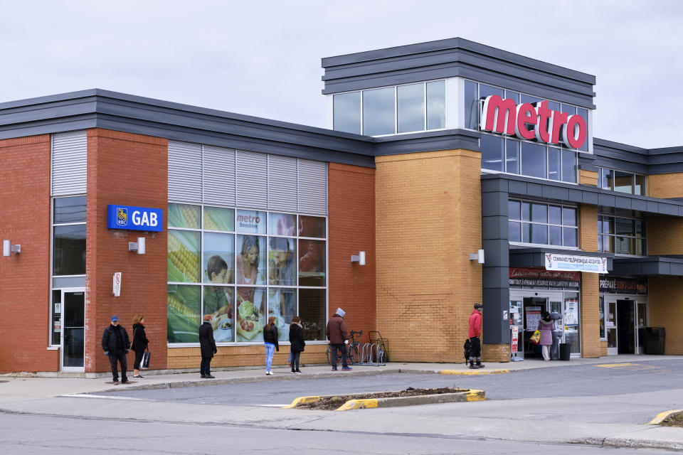 Montreal, Canada. April 11, 2020. People lining up with 2m social distancing before entering a Metro Grocery store on Easter Saturday.