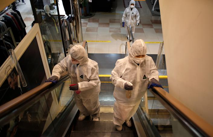 <br>Workers wearing protective gear spray disinfectant as a precaution against the new coronavirus at a department store in Seoul, South Korea, March 2, 2020.
