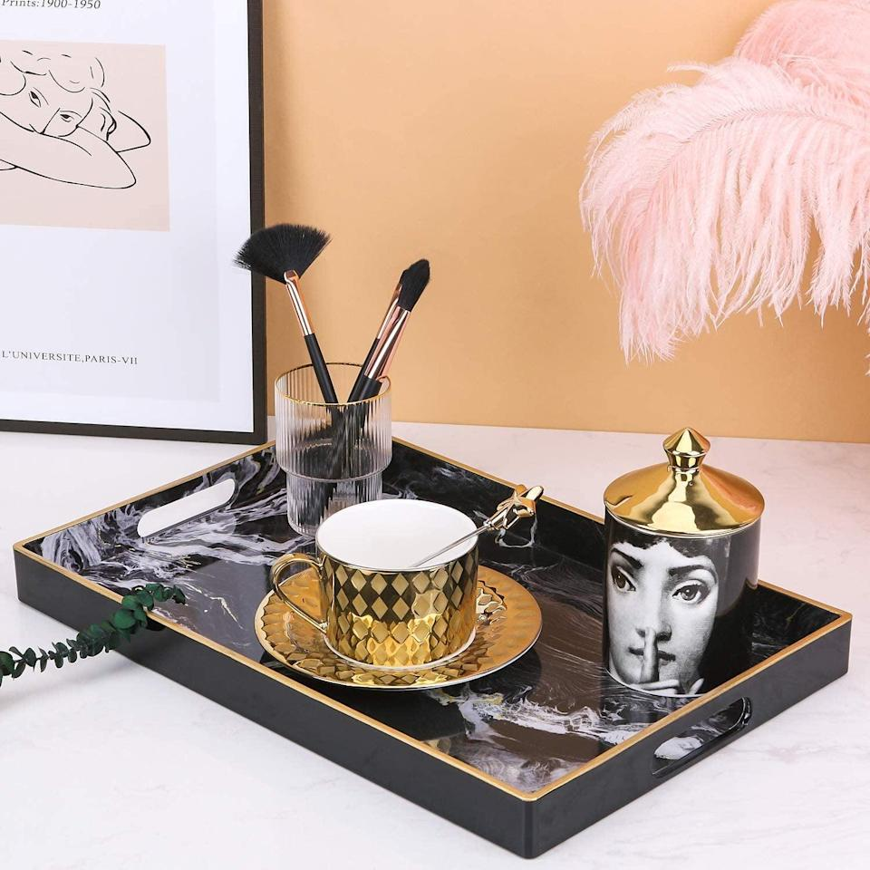 <p>The <span>Zosenley Decorative Vanity Tray</span> ($19) is sleek and portable.</p>