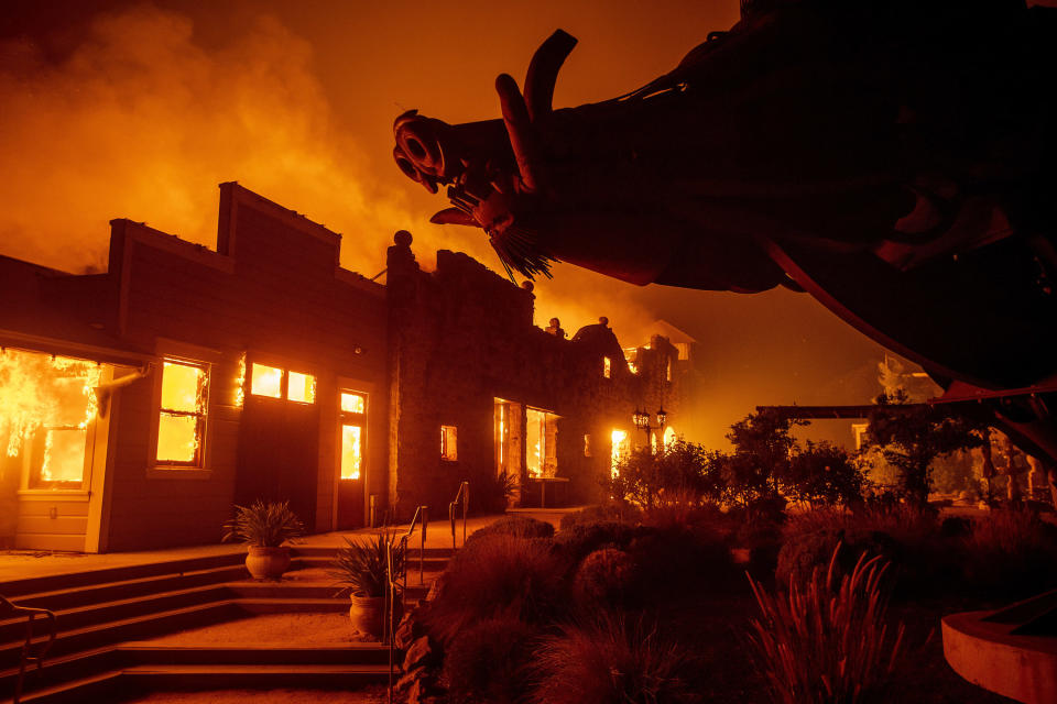 FILE - In this Oct. 27, 2019, file photo, flames from the Kincade Fire consume Soda Rock Winery in Healdsburg, Calif. A California prosecutor has charged troubled Pacific Gas & Electric with starting a 2019 wildfire. District Judge William Alsup overseeing Pacific Gas & Electric's criminal probation is holding a hearing Tuesday, May 4, 2021, to consider whether Pacific Gas & Electric violated its criminal probation from a fatal 2010 natural gas explosion by sparking the October 2019 Kincade Fire north of San Francisco.(AP Photo/Noah Berger, File)