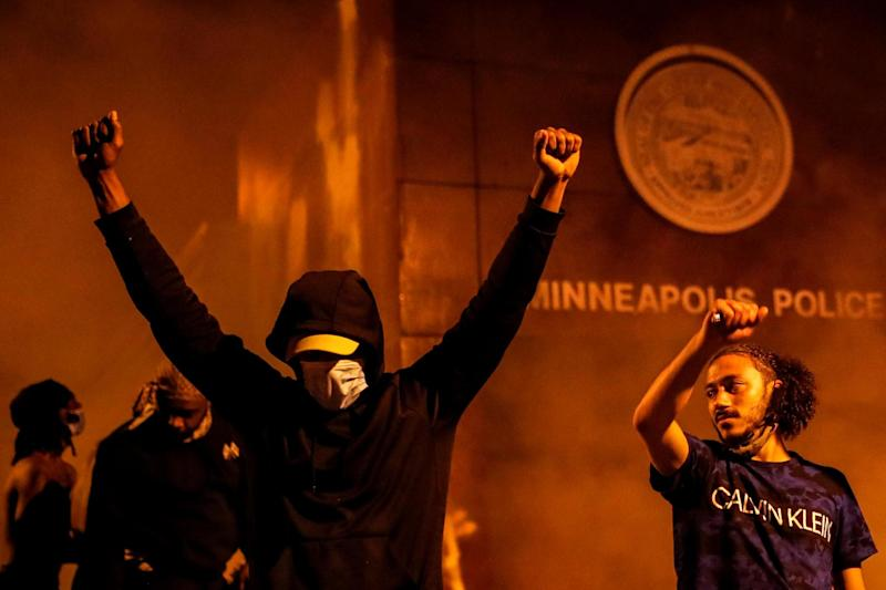 Protesters react after the entrance of a police station is set on fire during the demonstrations (REUTERS)