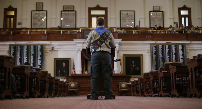 A Boy Scout reads a report from his home district to Gov. Rick Perry during the annual Boy Scouts Parade and Report to State in the House Chambers at the Texas State Capitol, Saturday, Feb. 2, 2013, in Austin, Texas. Perry says he hopes the Boy Scouts of America doesn't move soften its mandatory no-gays membership policy. (AP Photo/Eric Gay)