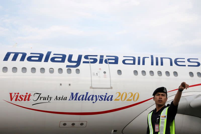 FILE PHOTO: An airport employee beside a Malaysia Airlines plane at Kuala Lumpur International Airport
