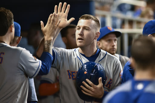 New York Mets third baseman Todd Frazier celebrates with teammates after scoring during the second inning of a baseball game against the Miami Marlins in Miami Sunday, July 1, 2018. (AP Photo/Gaston De Cardenas)